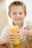 Jeune garçon à l'intérieur avec le jus d'orange Photographie stock libre de droits