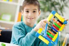 Jeune garçon à la maison travaillant à l'abaque Photo stock