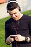 Jeune garçon écoutant la musique avec le smartphone dans la rue Image stock