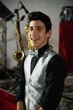 Jeune garçon élégant avec le noeud papillon de couleur argent, gilet de couleur argent, souriant, avant un concert musical photo stock