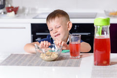 Jeune garçon éloignant le bol de céréale de petit déjeuner Photo stock