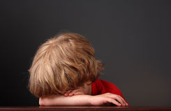 Jeune garçon étendant sa tête sur ses bras Image stock