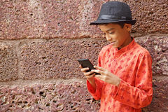 Jeune garçon appréciant Smartphone Photos libres de droits