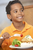 Jeune garçon appréciant un repas à la maison photos stock