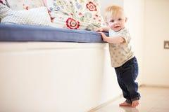 Jeune garçon apprenant à marcher en se tenant sur des meubles Photographie stock libre de droits