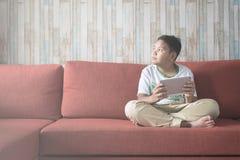 Jeune garçon asiatique à l'aide du comprimé numérique sur un sofa à la maison tout en regardant l'espace vide de copie de l'espac Photo libre de droits