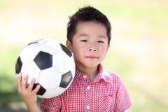 Jeune garçon asiatique avec du ballon de football Photo stock