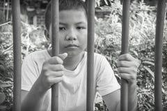 Jeune garçon asiatique emprisonné derrière des barres Images stock