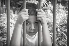 Jeune garçon asiatique emprisonné derrière des barres Image libre de droits