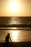Jeune garçon au voilier de observation de coucher du soleil dans la distance Photos stock