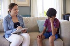 Jeune garçon avec des problèmes parlant avec le conseiller à la maison images libres de droits