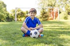 Jeune garçon avec du ballon de football sur un uniforme de sport photo libre de droits