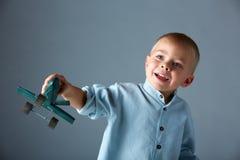 Jeune garçon avec l'avion en bois Photos stock