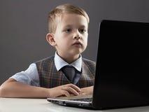 Jeune garçon avec l'ordinateur enfant regardant dans le carnet Photos stock