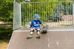 Jeune garçon avec la planche à roulettes se reposant sur la rampe Images libres de droits