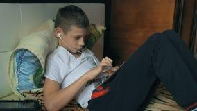 Jeune garçon avec la tablette dans la maison banque de vidéos