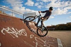 Jeune garçon avec le dirtbike dans le halfpipe Image libre de droits
