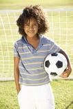 Jeune garçon avec le but se tenant prêt de ballon de football Image stock