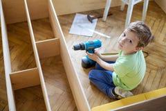 Jeune garçon avec le tournevis recherchant tout en se reposant sur le plancher Photo stock