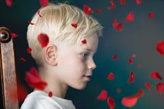 Jeune garçon avec les pétales de rose rouges en baisse Images stock