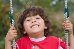 Jeune garçon balançant et souriant photo stock