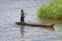 Jeune garçon barbotant une pirogue dans le lac Malawi Images libres de droits