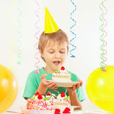 Jeune garçon blond dans le chapeau de fête avec le morceau de gâteau d'anniversaire Image stock