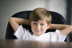 Jeune garçon blond enfoncé à une table. images stock