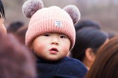 Jeune garçon chinois regardant au-dessus de son épaule du ` s de jour image libre de droits