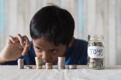 Jeune garçon comptant ses pièces de monnaie/épargne pour acheter les jouets rêveurs image stock