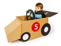Jeune garçon conduisant sa voiture de carton photos stock