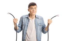Jeune garçon confus tenant un câble cassé image libre de droits