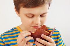 Jeune garçon coupé avec un petit pain de pomme sur la fin blanche de fond  images stock