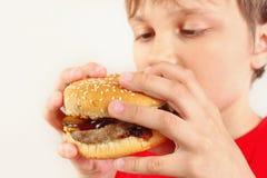 Jeune garçon coupé mangeant un hamburger savoureux sur la fin blanche de fond  image libre de droits