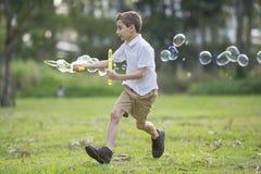 Jeune garçon courant avec la baguette magique de bulle photographie stock