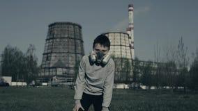 Jeune garçon couru contre des cheminées d'usine Concept de pollution atmosph?rique Portrait haut étroit de jeune usine de witn de banque de vidéos