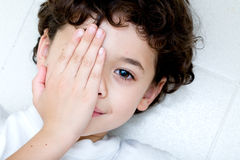 Jeune garçon couvrant un oeil. Photo stock