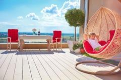 Jeune garçon détendant dans l'hamac sur le patio moderne de dessus de toit, terrasse à la maison photos libres de droits