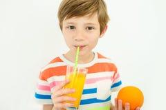 Jeune garçon d'adolescent buvant du jus d'orange à l'intérieur au fond blanc images stock