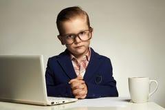 Jeune garçon d'affaires avec l'ordinateur Enfant drôle photographie stock libre de droits