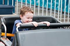 Jeune garçon d'enfant en bas âge ayant l'amusement sur le tour d'amusement de promenade Photo stock