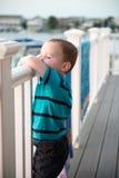 Jeune garçon d'enfant en bas âge sur la plate-forme de patio dehors au coucher du soleil vers le bas au rivage Photographie stock libre de droits