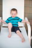 Jeune garçon d'enfant en bas âge sur la plate-forme de patio dehors au coucher du soleil vers le bas au rivage Image stock