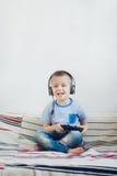 Jeune garçon dans l'écouteur jouant avec le playstation à la maison Image stock