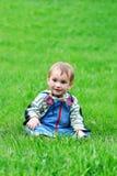Jeune garçon dans l'herbe verte photo stock