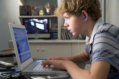 Jeune garçon dans la chambre à coucher utilisant l'ordinateur portatif écoutant le mp3 Photo stock