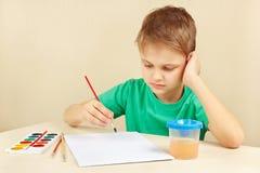 Jeune garçon dans la chemise verte allant peindre des aquarelles Image libre de droits