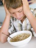 Jeune garçon dans la cuisine mangeant du potage photographie stock