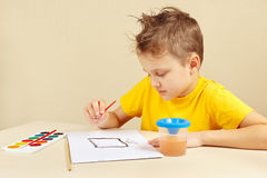 Jeune garçon dans la peinture jaune de chemise avec des aquarelles photo libre de droits