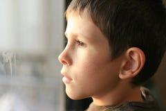 Jeune garçon dans la pensée avec la réflexion d'hublot photographie stock libre de droits